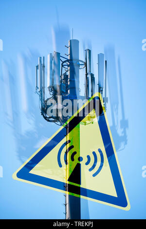 Broadcasting tower against blue sky and a hazard sign for Non-ionizing radiation , Germany - Stock Photo