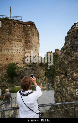 A woman taking a photo af an old church in Tbilisi. Georgia - Stock Photo