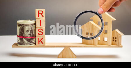 Money bag, blocks with the word Risk and a wooden house on the scales. The concept of losing money when investing in real estate. Risks of losing a ho - Stock Photo