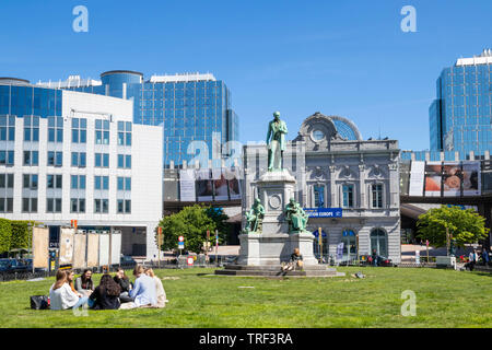 People on the grass in Place du Luxembourg PLUX Luxembourg Square Place du Luxembourg Ixelles statue of John Cockerill Brussels Belgium Eu Europe - Stock Photo