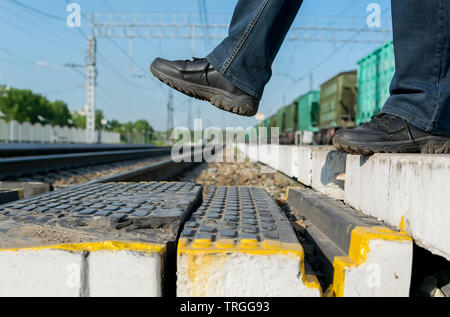 Pedestrian's feet step on a pedestrian crossing through the rails at the railway station on the background of freight cars - Stock Photo