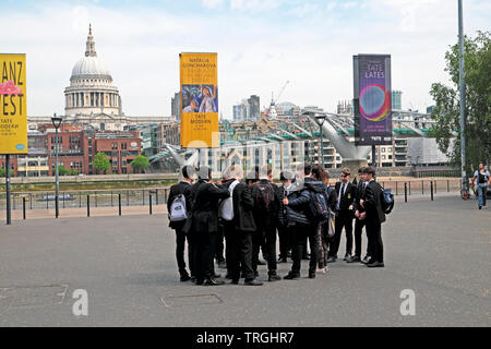 Group of school boys students pupils visiting the Tate Modern Art Gallery standing outside & view of St Pauls in South London England UK  KATHY DEWITT - Stock Photo