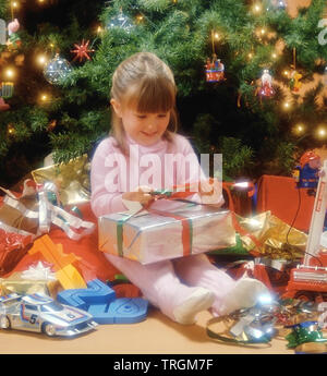 Little girl next to a Christmas tree opening presents - Stock Photo
