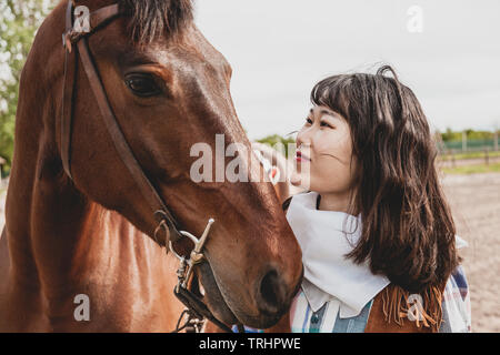 cute chinese cowgirl while taking care of her horse on a wild west farm - Stock Photo