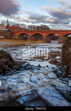 Kuldīga historical brick bridge viewed from Venta rapid. - Stock Photo