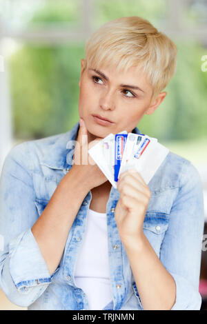 Woman looking concerned holding credit cards - Stock Photo