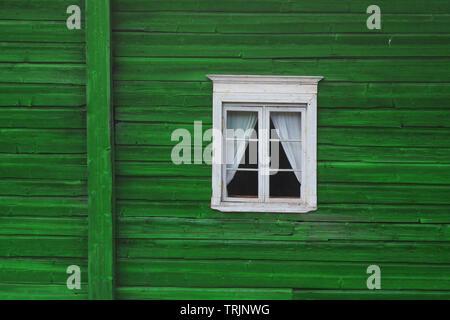 Green window on green wooden facade, photo taken in Finnland - Stock Photo