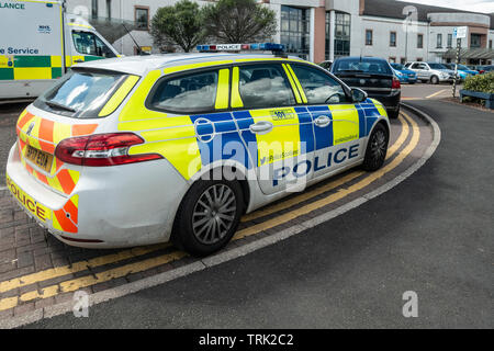 A police car and an ambulance parked outside the Accident and Emergency Unit of University Hospital Wishaw, Scotland. Car park and the Main Entrance. - Stock Photo