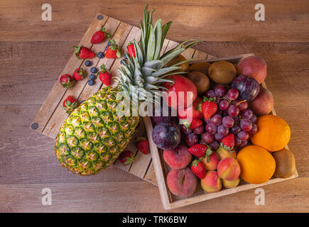 Fruit feast. Assorted fruits in a wooden box. Contains pineapple, grapes, apples, kiwis, oranges, apricots blueberries and strawberries. - Stock Photo