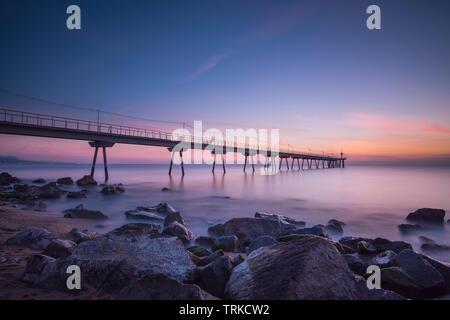 bridge on the beach at sunset - Stock Photo