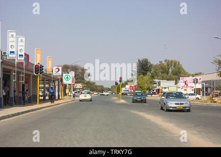 Okahandja in Namibia, Africa and its main road going through the centre of the small town with a few shops and people on the street during Winter - Stock Photo