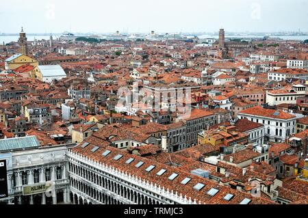 The rooftops of Venice with the port in the distance crowded with large cruise liners, Italy Europe EU - Stock Photo