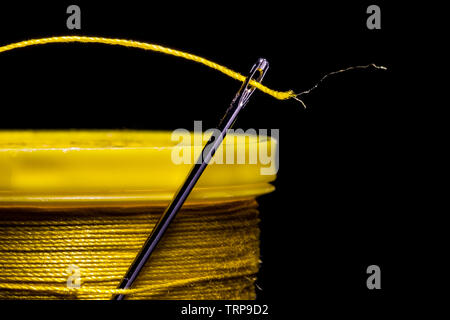 A macro image of a needle's eye threaded with a piece of yellow thread on a field of solid black.  The needle is entrapped in the thread wound on a sp - Stock Photo