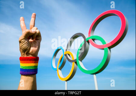 LONDON - MAY 4, 2019: A hand wearing gay pride rainbow colored wristband makes a peace sign in front of Olympic Rings standing under bright blue sky. - Stock Photo