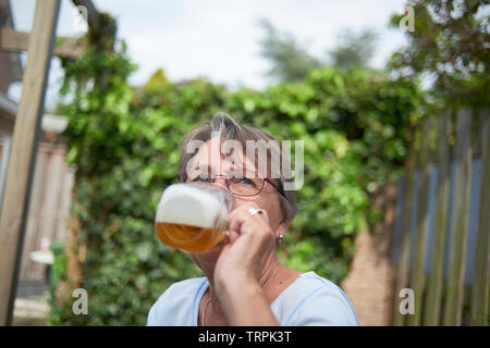 Happy and healthy elderly woman drinking a large glass of beer sitting outside in bright summer sunshine - Stock Photo