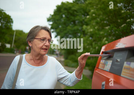 Happy and healthy elderly woman posting a letter in a red letterbox outside in bright summer sunshine - Stock Photo