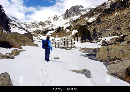 Hiker in valley in Sant Maurici National Park, Pyrenees Mountains, Catalunya (Catalonia), Spain - Stock Photo