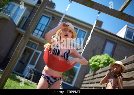 Cute young blonde caucasian girl sitting on a swing having fun with her best friend in summer sunshine - Stock Photo