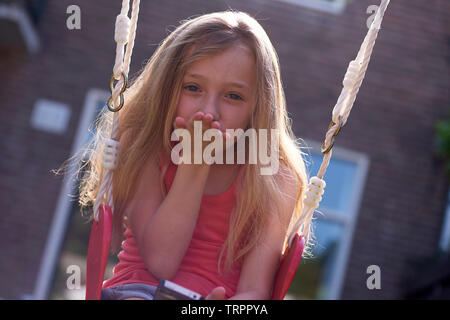 Cute young blonde caucasian girl sitting on a swing blowing a kiss into the camera - Stock Photo