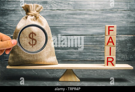 Money bag and wooden blocks with the word Fair. Balance. Fair value pricing, money debt. Fair deal. Reasonable price. Justified risk. Honest loan. Sec - Stock Photo