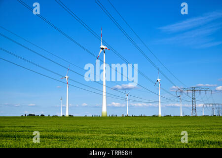Power lines and wind engines on a sunny day seen in Germany - Stock Photo