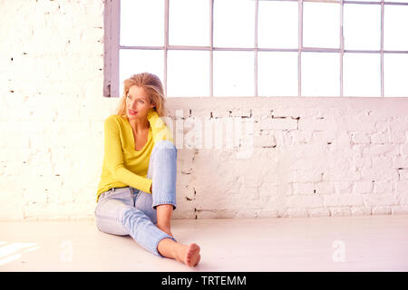 Beautiful middle aged woman deep in thought while sitting on the floor and relaxing. - Stock Photo