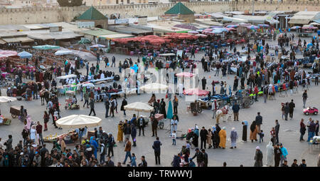 Wide angle view of El Hedim Square with restaurants, bars, countless market stalls and crowded with people and hawkers in the evening. Meknes, Morocco - Stock Photo