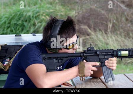A young man takes aim with an AR-15 style rifle at a Corpus Christi, Texas USA firing range. - Stock Photo