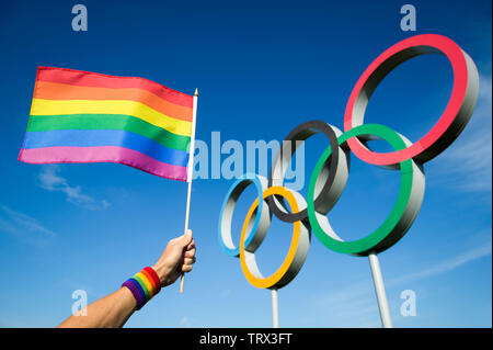 LONDON - MAY 4, 2019: A hand wearing rainbow colored sweatband waves a gay pride flag hangs in front of Olympic Rings against bright blue sky. - Stock Photo