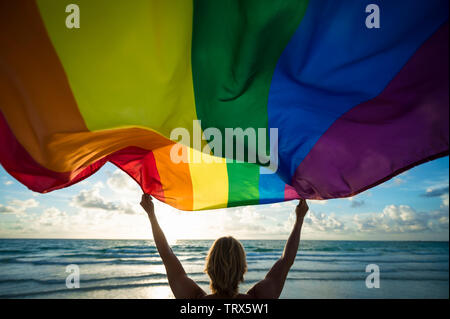 Colorful silhouette of a man with blond hair holding a gay pride rainbow flag blowing in the wind on a tropical beach with golden sun - Stock Photo
