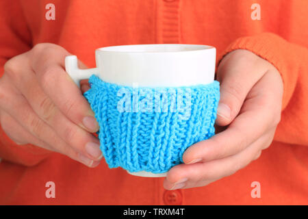 Cups with knitted things on it on wooden table close up - Stock Photo