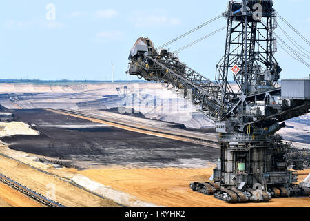 Bucket wheel excavator and wind turbines in the Garzweiler brown coal opencast mining in the Rhineland brown coal mining area. - Stock Photo
