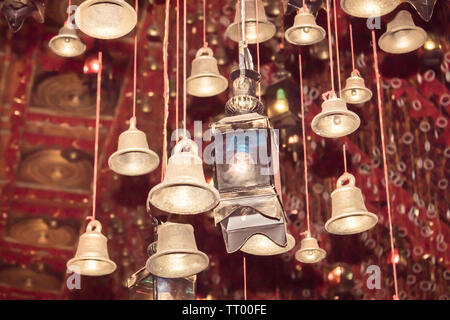 Golden bells with greeting lucky word on red ribbon at Dakshineswar Kali Temple Kolkata. Pilgrims people wish and hang it on rope for pray. Merry chri - Stock Photo