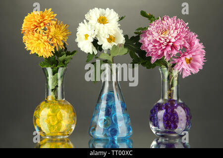 Beautiful flowers in vases with hydrogel on table on gray background - Stock Photo