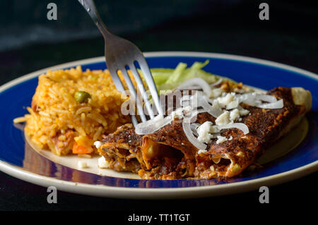 Mexican enmoladas, enchiladas topped with mole sauce and queso fresco, served with rice and salad. Isolated on dark background with copy space - Stock Photo