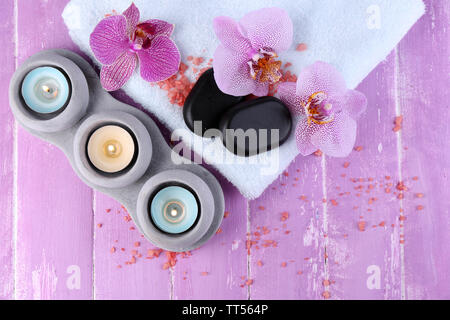 Orchid flowers, spa stones, candles and towel on color wooden background - Stock Photo