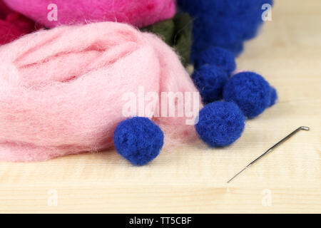 Wool for felting with needle on wooden background - Stock Photo
