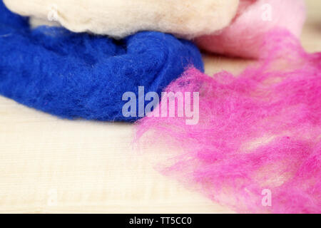 Multicolored wool for felting on wooden background - Stock Photo