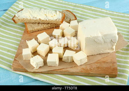 Fresh butter on cutting board and homemade bread, on color wooden background - Stock Photo