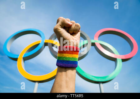 LONDON - MAY 4, 2019: A hand wearing gay pride rainbow colored wristband makes a celebratory fist in front of Olympic Rings standing under blue sky. - Stock Photo