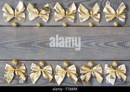 Two rows of golden bows and glitter globules on wooden background - side lighting - Stock Photo