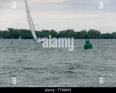 Toronto, Canada. 15th June, 2019. Yacht sailing around buoy on Lake Ontario, leaning to the side under high wind. - Stock Photo