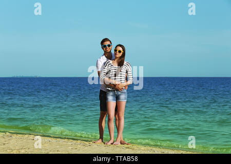 Beautiful young couple on beach - Stock Photo