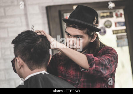 portrait of professional Asian man with long brown hair work as barber trimming his costumer with scissors and comb in barbershop - Stock Photo