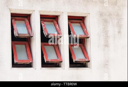 Row of Old Red Wooden Awning Windows Frame Open in The Morning for Bright Light Streaming Through The Room. - Stock Photo