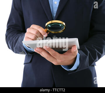 Businessman holding magnifying glass and digital tablet, isolated on white, searching and examining concept - Stock Photo