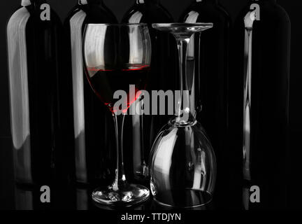 Wine glasses against bottles in a row on black background, close up - Stock Photo
