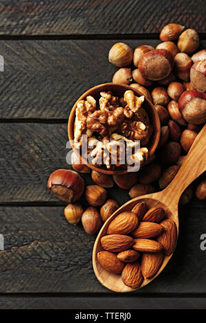 A wooden spoon, a bowl, hazelnuts, walnuts, almonds and acorns on the wooden table - Stock Photo