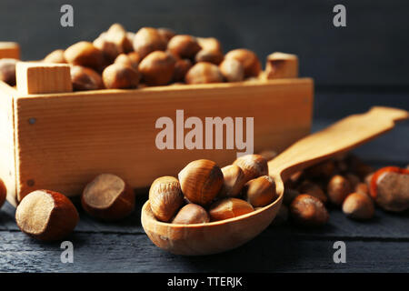Hazelnuts in wooden box and spoon on the table, close-up - Stock Photo