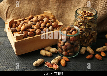 Mix of nuts in the glass jars and wooden box, on the table - Stock Photo
